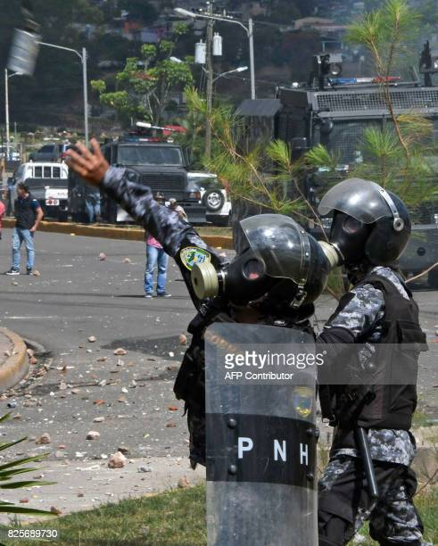 A member of the riot police throws a tear gas canister to students from the National Autonomous University of Honduras gathered under the University...