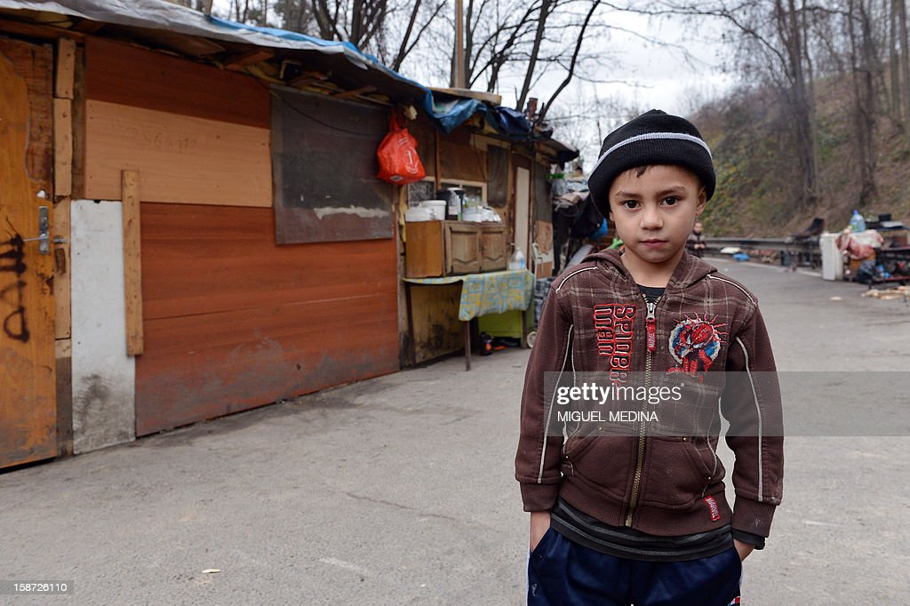 A member of the Roma community stands near shanty houses on the periphery of Paris on December 26, 2012. AFP PHOTO / Miguel Medina