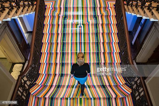A member of the Royal Academy staff walks on British artist Jim Lambie's installation 'Zobop' during the press preview of the Royal Academy Summer...