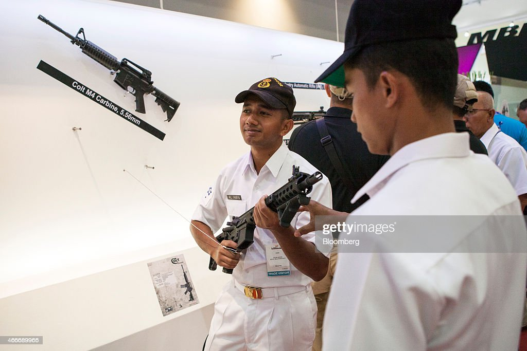 A member of the Royal Malaysian Navy center stands with a Colt Defense Co M4 Carbine semiautomatic rifle at the SME Ordnance BHd booth during the...