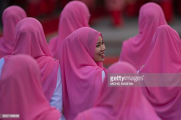 TOPSHOT A member of the ruling party United Malays National Organisation smiles as she looks on before the opening ceremony of the party's annual...