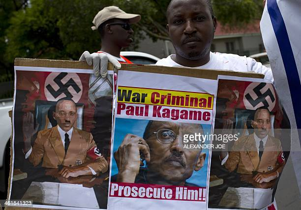 A member of the Rwanda National Congress opposition party holds a picture and sketches of Rwandan President Paul Kagame portrayed as a Nazi leader...