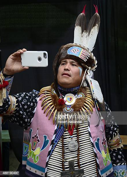 A member of the Sac and Fox Indian tribe takes a 'selfie' photograph of himself with his Apple iPhone while waiting to participate in the annual...