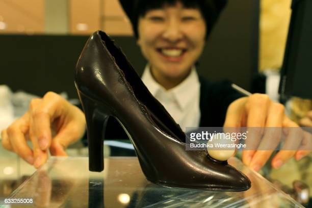 A member of the sales staff stand next to a ladies shoe made of chocolate for Valentine's Day at a Takashimaya Department Store on February 1 2017 in...