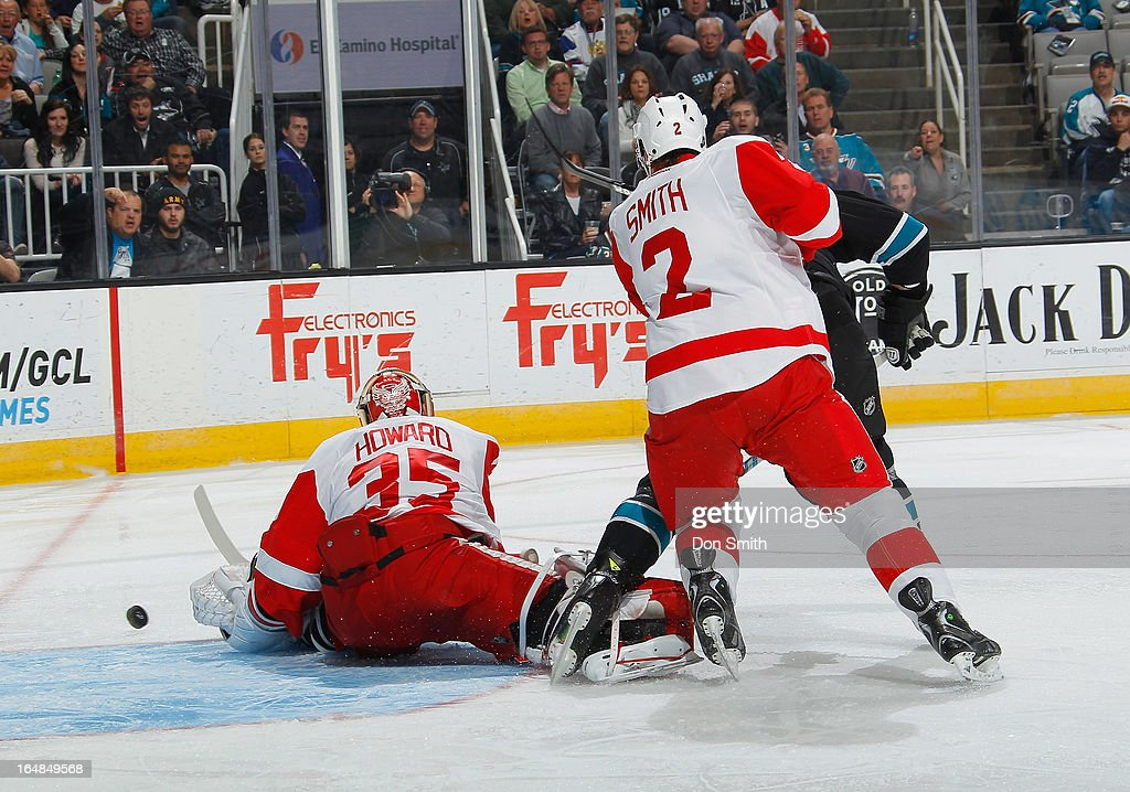 A member of the San Jose Sharks battles for the puck against Brendan Smith #2 and <a gi-track='captionPersonalityLinkClicked' href=/galleries/search?phrase=Jimmy+Howard&family=editorial&specificpeople=2118637 ng-click='$event.stopPropagation()'>Jimmy Howard</a> #35 of the Detroit Red Wings during an NHL game on March 28, 2013 at HP Pavilion in San Jose, California.