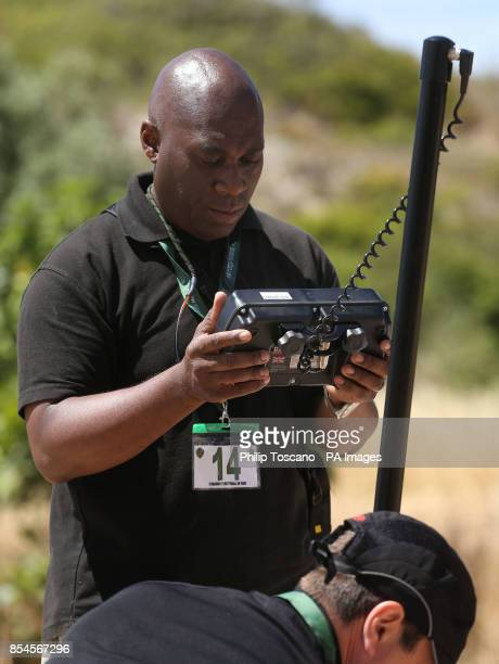 A member of the search team looks at a screen while a camera is placed inside an drain next to an area of wasteland during the search for evidence of...