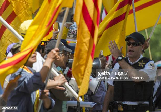 A member of the Secret Service pushes protesters who hold Vietnamese red flags with gold star designed in 1940 and used during an uprising against...