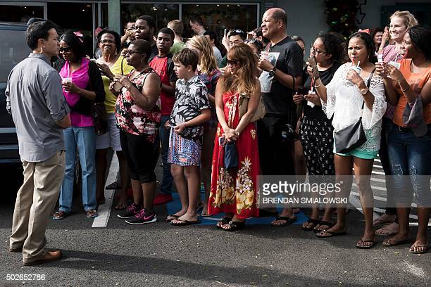 A member of the Secret Service stands watch over a crowd as US President Barack Obama stops for shaved ice from Island Snow after a visit to the...