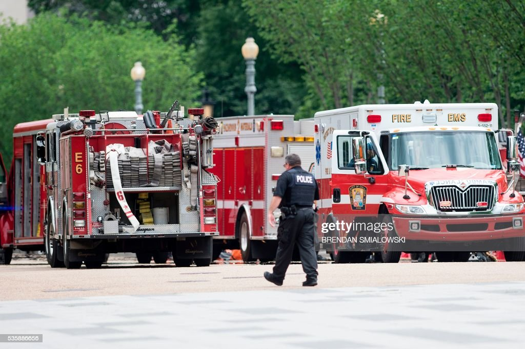 A member of the Secret Service walks past firetrucks and ambulances on Pennsylvania Avenue during a security lockdown of the White House grounds May 30, 2016 in Washington, DC. / AFP / Brendan Smialowski