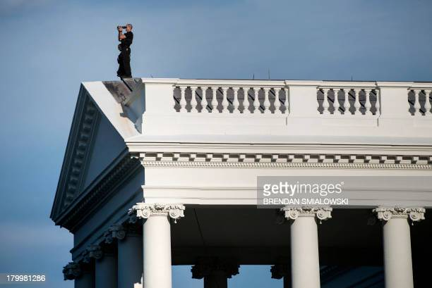 A member of the Secret Service's counter sniper team looks out from the roof of the North Portico of the White House September 7 2013 in Washington...