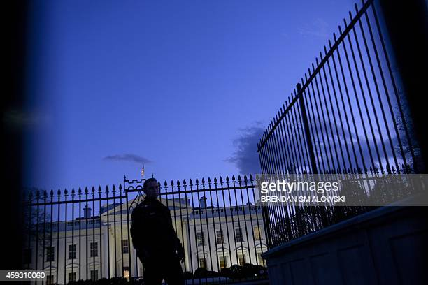A member of the Secret Service's uniformed division stands by a fence in front of the White House November 20 2014 in Washington DC Obama is expected...