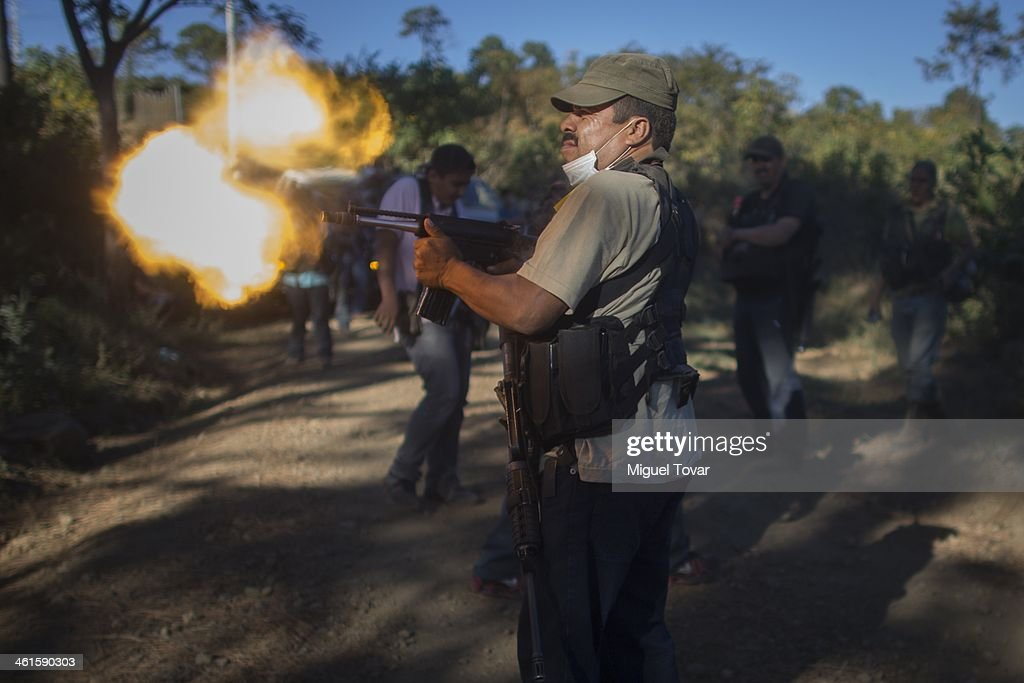 A member of the self-defense group tests his weapon at the outskirt of Paracuaro, in the state of Michoacan, Mexico. Despite some success by self-defense groups to free a few municipalities from the Knights Templar cartel, the cartel continues to enforce a stranglehold on other parts of Michoacan, a rich farming state that is a major exporter of lime, avocado and mango on January 08, 2014 in Mexico Paracuaro, Mexico.