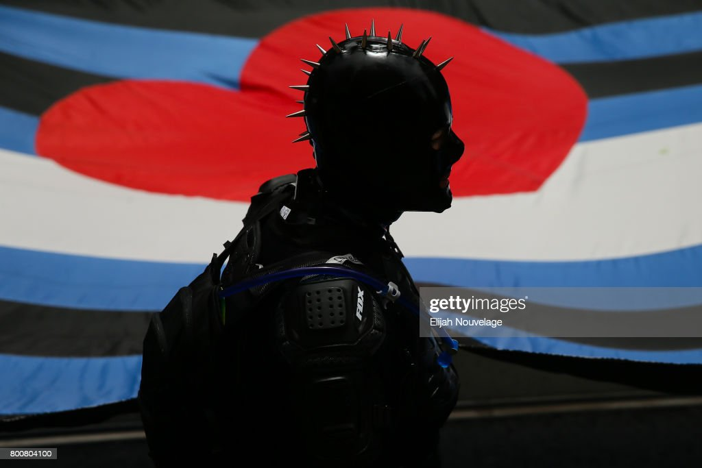 A member of the SF Leather contingent is silhouetted against a large flag while participating in the annual LGBTQI Pride Parade on June 25, 2017 in San Francisco, California.