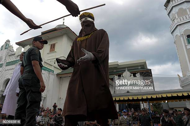 A member of the sharia police receives a cane as officials conduct punishment based on Islamic sharia law in Banda Aceh on December 28 2015 Aceh is...