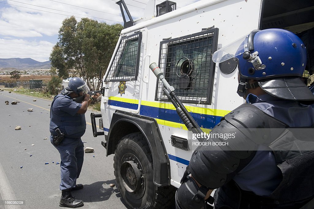 A member of the South African Police Services(L) fires rubber bullets at striking farmworkers (not visible), while another officer gets ready to fire a tear-gas grenade, during violent clashes, on January 10, 2013 in De Doorns, a small farming town about 140Km North of Cape Town, South Africa. The farm workers have said that they they will not return to work on the fruit growing region's farms until they receive a daily wage of at least R150($17) per day, which is about double what they currently earn. AFP PHOTO / RODGER BOSCH