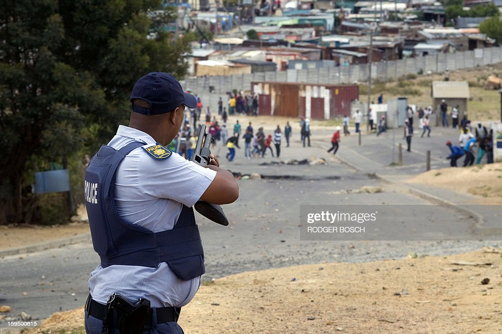 A member of the South African Police Services gets ready to fire rubber bullets at rock-throwing protestors during a strike by farmworkers, on January 14, 2012, in Villiersdorp, a small farming town about 100Km North of Cape Town, South Africa. The farm workers have said that they they will not return to work on the fruit growing region's farms until they receive a daily wage of at least R150($17) per day. The strike has affected many rural towns in the Western Cape Province, with widespread violence. BOSCH