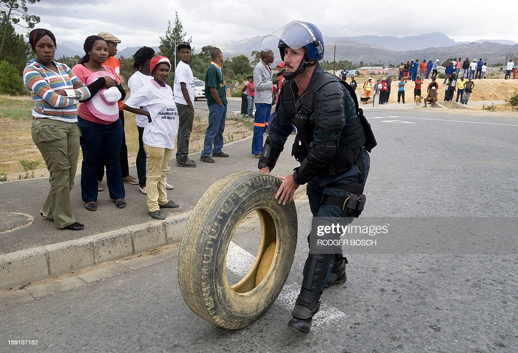 A member of the South African Police Services rolls a car tyre away from a group of striking farmworkers on January 9, 2013 in Wolseley, a small rural town about 120Km North of Cape Town, South Africa. Strikers have used tyres to set up burning barricades during their protests. Workers have said they will not return to the fruit growing region's farms until they receive a daily wage of at least $17 (13 euros) per day. AFP / RODGER