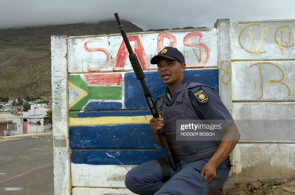 A member of the South African Police Services(SAPS) takes cover behind a wall from rocks being thrown by protestors (not visible) during an illegal strike by farmworkers, on January 14, 2012 in Villiersdorp, a small farming town about 100Km North of Cape Town, South Africa. The farm workers have said that they they will not return to work on the fruit growing region's farms until they receive a daily wage of at least R150($17) per day. The colours of the SAPS are painted on the wall behind the officer. BOSCH