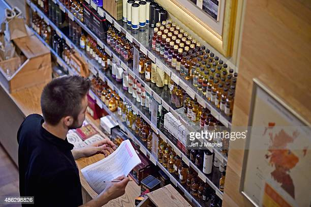 A member of the staff views whisky for sale at The Scotch Whisky Experience on September 3 2015 in EdinburghScotlandPlans to introduce a minimum unit...