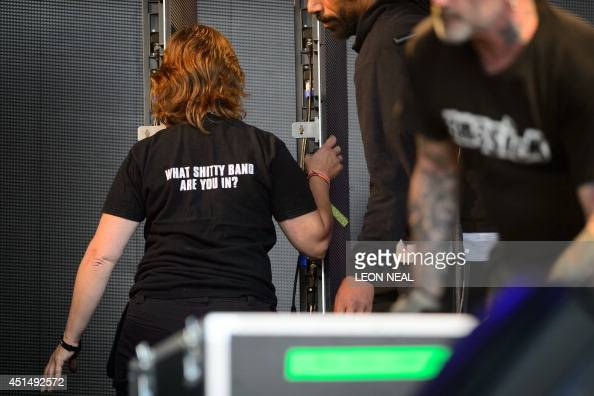 A member of the stage crew wears a brusque shirt logo on the Pyramid Stage on the second day of the Glastonbury Festival of Music and Performing Arts...