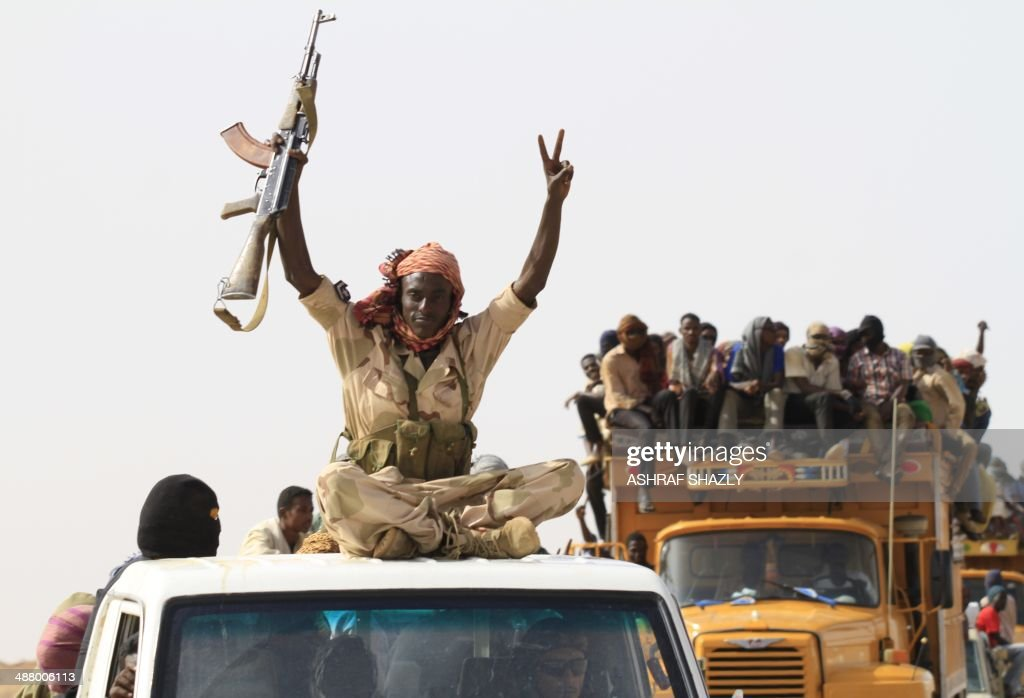 A member of the Sudanese military flashes the sign for victory as a convoy of vehicles carrying illegal migrants who were abandoned in the desert by...