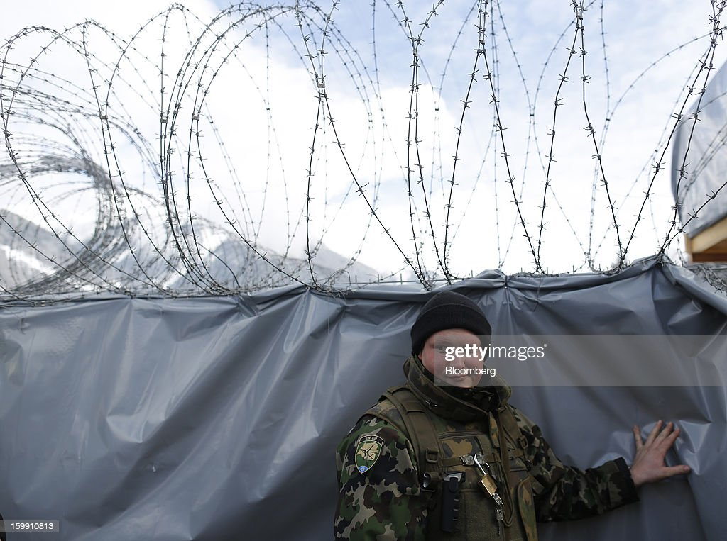 A member of the Swiss army stands by a security barrier near to the Congress Center, the venue for the World Economic Forum (WEF) in Davos, Switzerland, on Tuesday, Jan. 22, 2013. As policy makers and executives debate the latest remedies to draw a line under Europe's worst crisis since World War II, Swiss officers are now using the World Economic Forum as a testing ground for plans to turn the entire country into a fortress. Photographer: Simon Dawson/Bloomberg via Getty Images