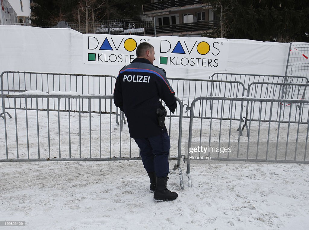 A member of the Swiss police force moves a security barrier into position outside the Congress Centre ahead of the World Economic Forum (WEF) meeting in Davos, Switzerland, on Monday, Jan. 21, 2013. This week the business elite gathers in the Swiss Alps for the 43rd annual meeting of the World Economic Forum in Davos, the five day event runs from Jan. 23-27. Photographer: Simon Dawson/Bloomberg via Getty Images