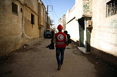 A member of the Syrian Arab Red Crescent carries a wounded boy following an airstrike in the rebelheld city of Douma in Eastern Ghouta on February 26...