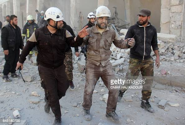 TOPSHOT A member of the Syrian civil defence known as the White Helmets reacts after an air strike during a rescue operation in the rebelheld town of...