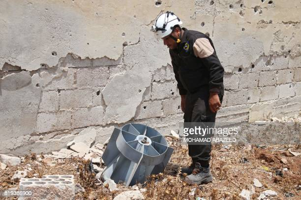 A member of the Syrian civil defence volunteers also known as the White Helmets stands next to the tail fin of a bomb as local bombdisposal experts...