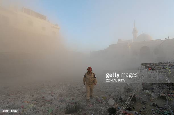 A member of the Syrian Civil Defence walks through a cloud of dust after an alleged air strike by Syrian government forces in the northern Syrian...