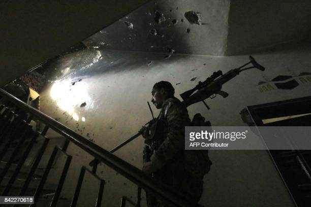 TOPSHOT A member of the Syrian Democratic Forces a US backed KurdishArab alliance patrols inside a building in an area close to the Old City in the...