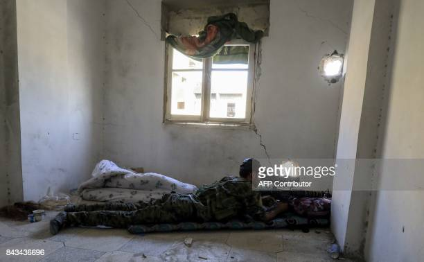 TOPSHOT A member of the Syrian Democratic Forces a US backed KurdishArab alliance looks through the scope of a sniper rifle as he lies in a flat in...