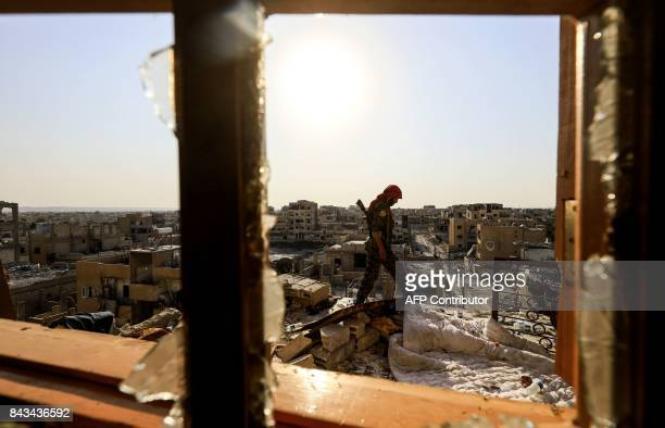 TOPSHOT A member of the Syrian Democratic Forces a US backed KurdishArab alliance walks on the roof of a building in the western alDaraiya...