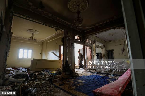 TOPSHOT A member of the Syrian Democratic Forces a US backed KurdishArab alliance walks through a damaged flat in a building in the western alDaraiya...