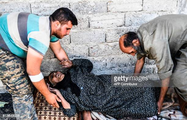 A member of the Syrian Democratic Forces an alliance of Kurdish and Arab fighters helps wounded Syrians on the front line in eastern Raqa on July 13...
