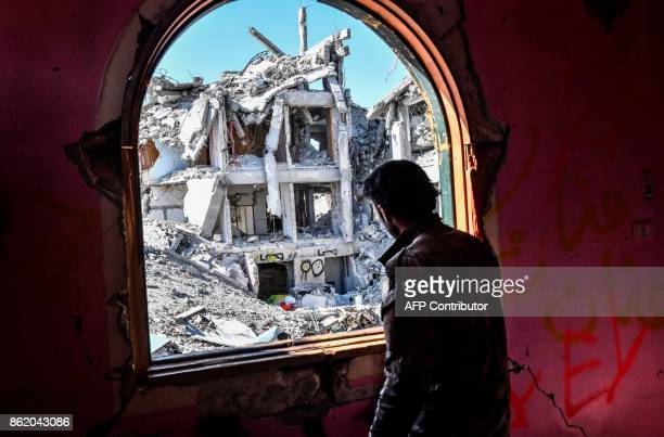 TOPSHOT A member of the Syrian Democratic Forces backed by US special forces looks out from a building at the frontline in Raqa on October 16 2017 in...