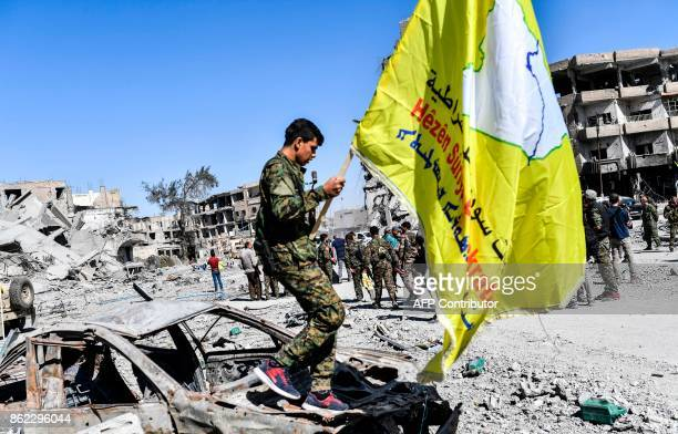 TOPSHOT A member of the Syrian Democratic Forces backed by US special forces walks with their flag at the iconic AlNaim square in Raqa on October 17...