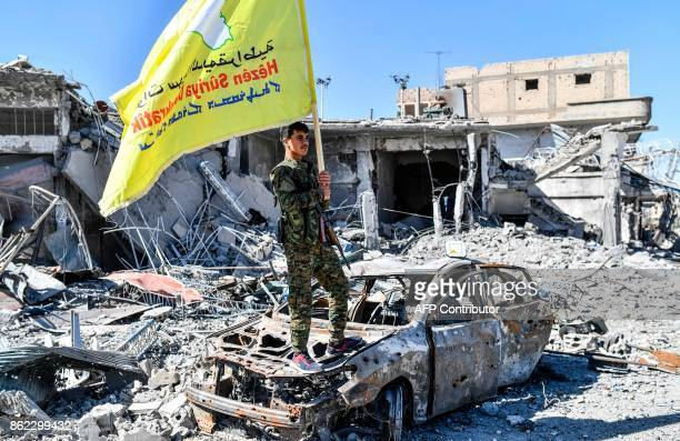 A member of the Syrian Democratic Forces backed by US special forces holds their flag at the iconic AlNaim square in Raqa on October 17 2017 USbacked...