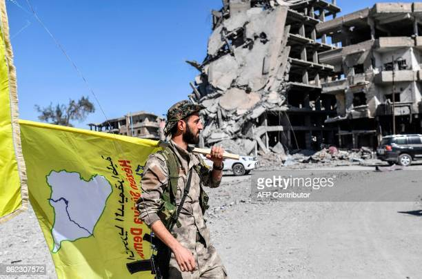 A member of the Syrian Democratic Forces backed by US special forces carries his group's flag at the iconic AlNaim square in Raqa on October 17 2017...