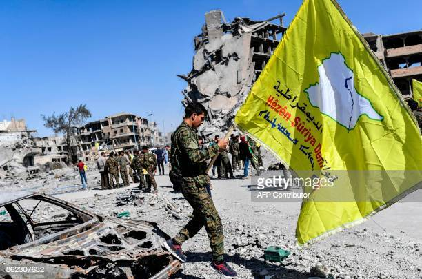 A member of the Syrian Democratic Forces backed by US special forces waves his group's flag at the iconic AlNaim square in Raqa on October 17 2017...