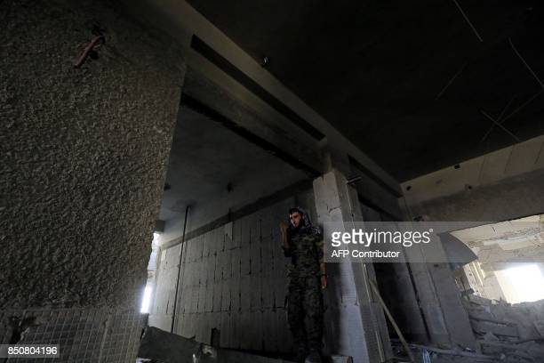 TOPSHOT A member of the Syrian Democratic Forces clears a building in the former Islamic State stronghold of Raqa on September 21 2017 Syrian...