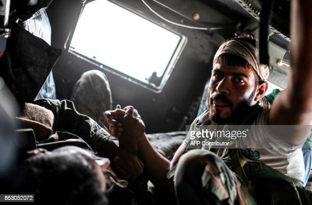 TOPSHOT A member of the Syrian Democratic Forces comforts his wounded comrade Ibrahim who was shot by a sniper as they drive towards a medical centre...