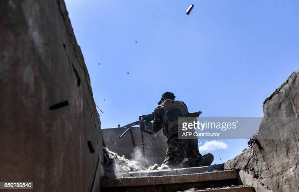 TOPSHOT A member of the Syrian Democratic Forces fires his machine gun during clashes with Islamic State group jihadists near the central hospital of...