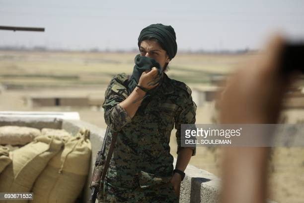 CORRECTION A member of the Syrian Democratic Forces made up of an alliance of Kurdish and Arab fighters poses for a photo some two kilometres from...