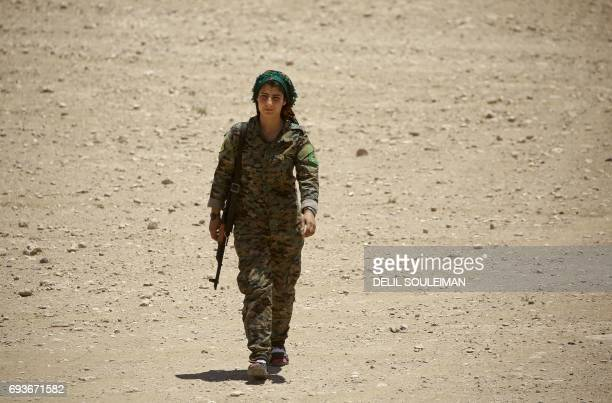 CORRECTION A member of the Syrian Democratic Forces made up of an alliance of Kurdish and Arab fighters walks some two kilometres from the AlMeshleb...