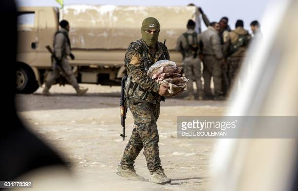 TOPSHOT A member of the Syrian Democratic Forces made up of USbacked Kurdish and Arab fighters carries supplies near the village of Bir Fawaz 20 km...