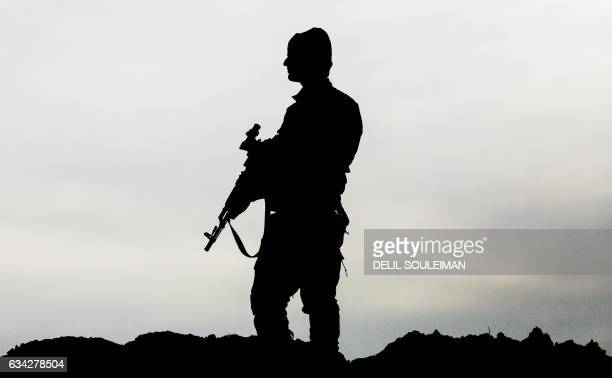 TOPSHOT A member of the Syrian Democratic Forces made up of USbacked Kurdish and Arab fighters stands guard near the village of Bir Fawaz 20 km north...