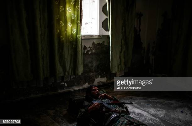 TOPSHOT A member of the Syrian Democratic Forces sleep inside a building on the eastern frontline of Raqa on September 24 2017 Syrian fighters backed...