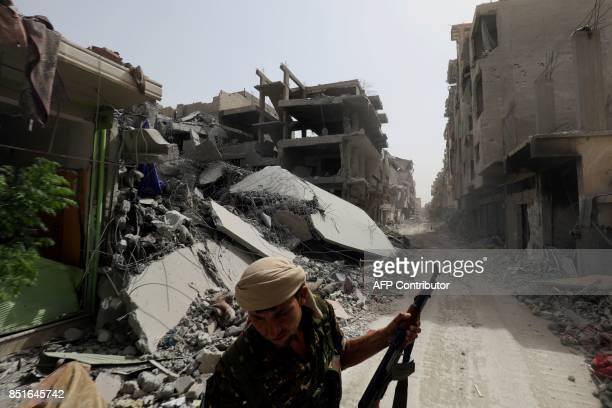 A member of the Syrian Democratic Forces stands on a damaged street in the former Islamic State stronghold of Raqa on September 22 as the Syrian...